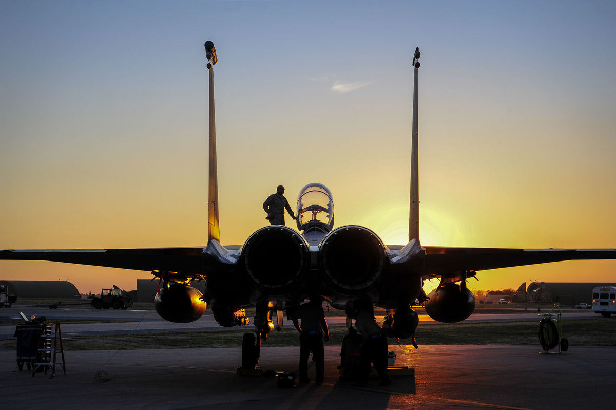 Cory Bush / U.S. Department of Defense, stands on a fighter plane readying to enter the pilot seat.
